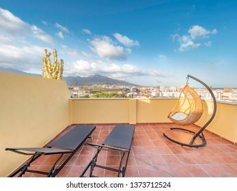 Hanging chair and sun beds in a sunny terrace of a relaxing summer holiday destination with sea view.