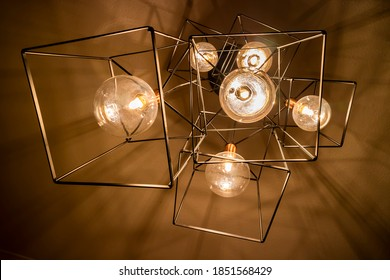 Hanging cube lighting in the dining room adding a moody and cozy ambiance lighting during dinner with the family.
