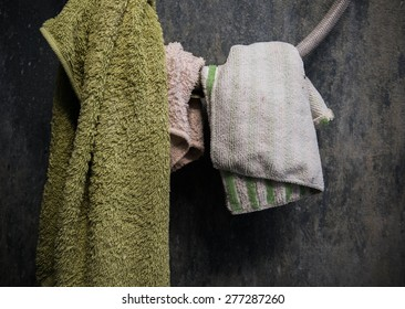Hanging dirty towel and cotton on shower wire with dirty grunge concrete wall in toilet