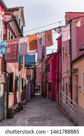 Hanging drying wet clothes and colorful traditional houses of Burano island, Venice. Hung multicolor clothes drying in Burano, Venezia.
