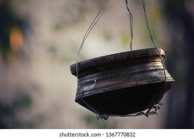 Hanging earthen pot on tree fill with water for birds.