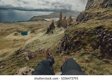 Hanging feet from the edge of a cliff near Old man Of Storr