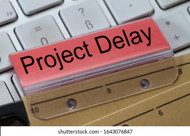 hanging file on a keyboard with red label written: Projekt Delay