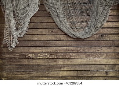Hanging Fishnet On The Rustic Wood Slats Wall Background. Grunge Wooden Background With Old Fish Net
