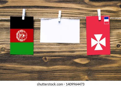 Hanging flags of Afghanistan and Wallis And Futuna attached to rope with clothes pins with copy space on white note paper on wooden background.Diplomatic relations between countries.
