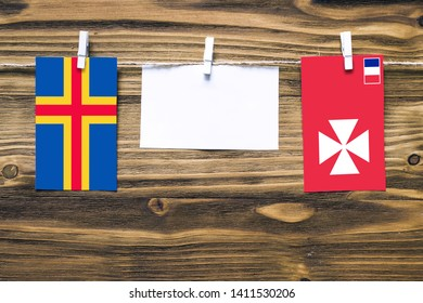 Hanging flags of Aland Islands and Wallis And Futuna attached to rope with clothes pins with copy space on white note paper on wooden background.Diplomatic relations between countries.
