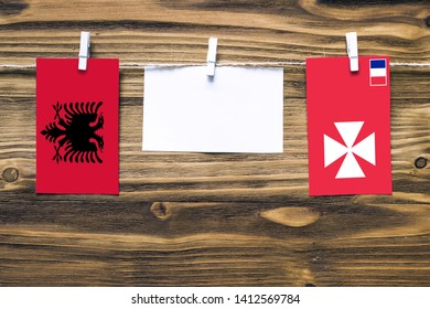 Hanging flags of Albania and Wallis And Futuna attached to rope with clothes pins with copy space on white note paper on wooden background.Diplomatic relations between countries.
