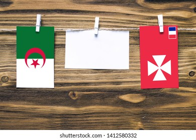 Hanging flags of Algeria and Wallis And Futuna attached to rope with clothes pins with copy space on white note paper on wooden background.Diplomatic relations between countries.