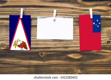 Hanging flags of American Samoa and Samoa attached to rope with clothes pins with copy space on white note paper on wooden background.Diplomatic relations between countries.