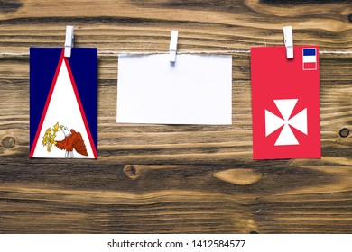 Hanging flags of American Samoa and Wallis And Futuna attached to rope with clothes pins with copy space on white note paper on wooden background.Diplomatic relations between countries.