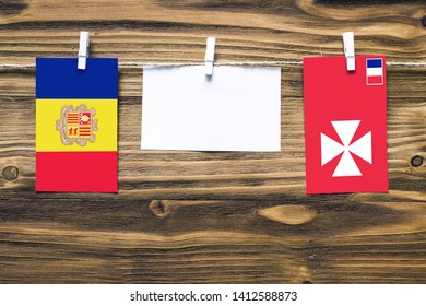 Hanging flags of Andorra and Wallis And Futuna attached to rope with clothes pins with copy space on white note paper on wooden background.Diplomatic relations between countries.