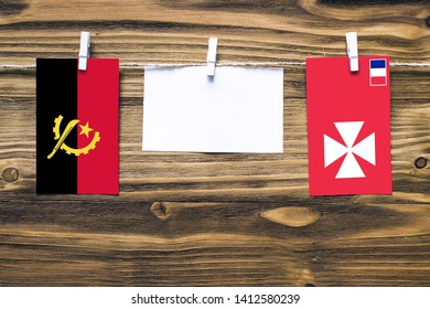 Hanging flags of Angola and Wallis And Futuna attached to rope with clothes pins with copy space on white note paper on wooden background.Diplomatic relations between countries.