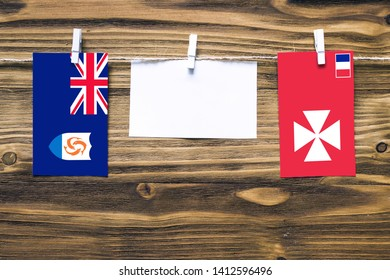 Hanging flags of Anguilla and Wallis And Futuna attached to rope with clothes pins with copy space on white note paper on wooden background.Diplomatic relations between countries.