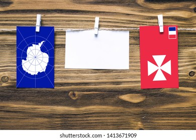 Hanging flags of Antarctica and Wallis And Futuna attached to rope with clothes pins with copy space on white note paper on wooden background.Diplomatic relations between countries.