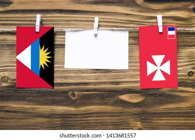 Hanging flags of Antigua and Barbuda and Wallis And Futuna attached to rope with clothes pins with copy space on white note paper on wooden background.Diplomatic relations between countries.