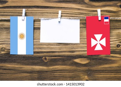 Hanging flags of Argentina and Wallis And Futuna attached to rope with clothes pins with copy space on white note paper on wooden background.Diplomatic relations between countries.