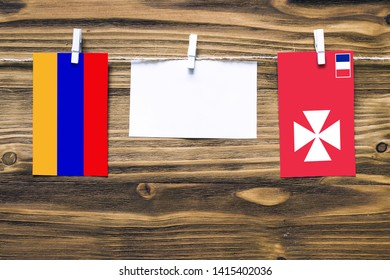 Hanging flags of Armenia and Wallis And Futuna attached to rope with clothes pins with copy space on white note paper on wooden background.Diplomatic relations between countries.