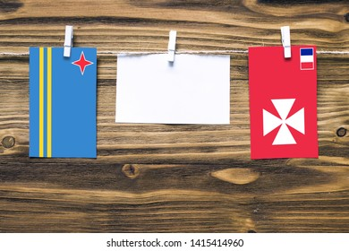 Hanging flags of Aruba and Wallis And Futuna attached to rope with clothes pins with copy space on white note paper on wooden background.Diplomatic relations between countries.