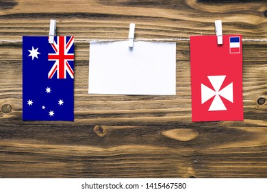 Hanging flags of Australia and Wallis And Futuna attached to rope with clothes pins with copy space on white note paper on wooden background.Diplomatic relations between countries.