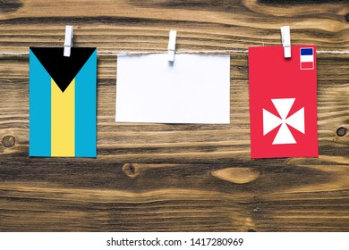 Hanging flags of Bahamas and Wallis And Futuna attached to rope with clothes pins with copy space on white note paper on wooden background.Diplomatic relations between countries.
