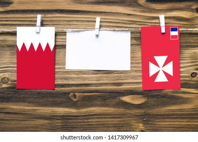 Hanging flags of Bahrain and Wallis And Futuna attached to rope with clothes pins with copy space on white note paper on wooden background.Diplomatic relations between countries.