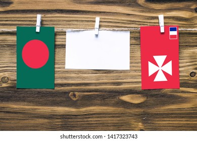 Hanging flags of Bangladesh and Wallis And Futuna attached to rope with clothes pins with copy space on white note paper on wooden background.Diplomatic relations between countries.