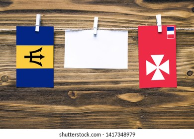 Hanging flags of Barbados and Wallis And Futuna attached to rope with clothes pins with copy space on white note paper on wooden background.Diplomatic relations between countries.