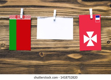 Hanging flags of Belarus and Wallis And Futuna attached to rope with clothes pins with copy space on white note paper on wooden background.Diplomatic relations between countries.