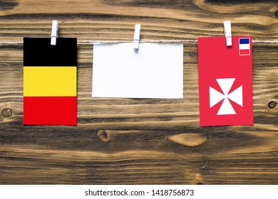 Hanging flags of Belgium and Wallis And Futuna attached to rope with clothes pins with copy space on white note paper on wooden background.Diplomatic relations between countries.