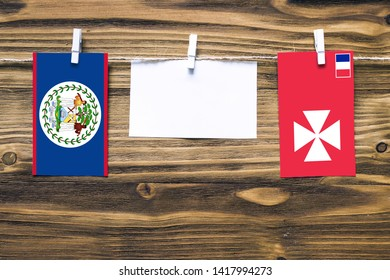 Hanging flags of Belize and Wallis And Futuna attached to rope with clothes pins with copy space on white note paper on wooden background.Diplomatic relations between countries.
