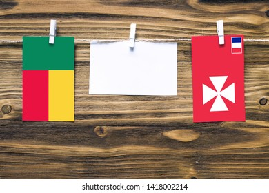 Hanging flags of Benin and Wallis And Futuna attached to rope with clothes pins with copy space on white note paper on wooden background.Diplomatic relations between countries.