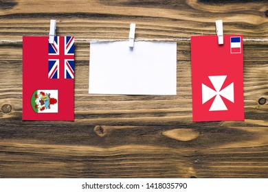 Hanging flags of Bermuda and Wallis And Futuna attached to rope with clothes pins with copy space on white note paper on wooden background.Diplomatic relations between countries.