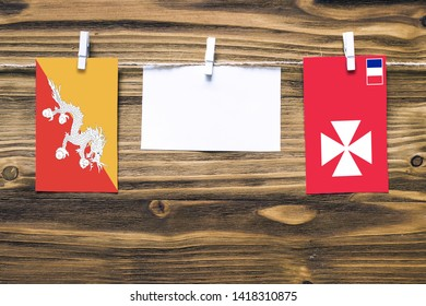 Hanging flags of Bhutan and Wallis And Futuna attached to rope with clothes pins with copy space on white note paper on wooden background.Diplomatic relations between countries.