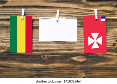 Hanging flags of Bolivia and Wallis And Futuna attached to rope with clothes pins with copy space on white note paper on wooden background.Diplomatic relations between countries.