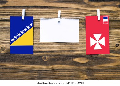 Hanging flags of Bosnia Herzegovina and Wallis And Futuna attached to rope with clothes pins with copy space on white note paper on wooden background.Diplomatic relations between countries.