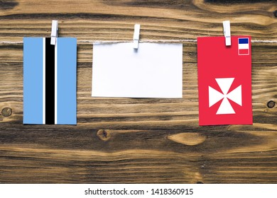 Hanging flags of Botswana and Wallis And Futuna attached to rope with clothes pins with copy space on white note paper on wooden background.Diplomatic relations between countries.