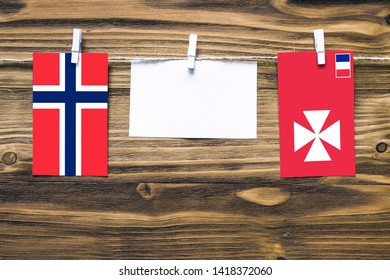 Hanging flags of Bouvet Islands and Wallis And Futuna attached to rope with clothes pins with copy space on white note paper on wooden background.Diplomatic relations between countries.