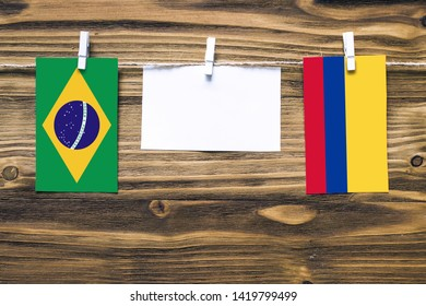 Hanging flags of Brazil and Colombia attached to rope with clothes pins with copy space on white note paper on wooden background.Diplomatic relations between countries.