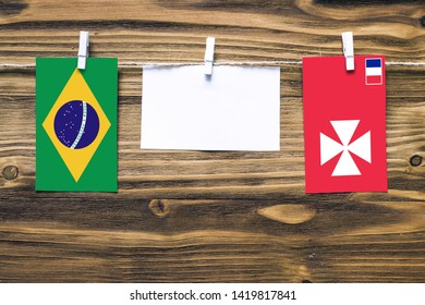Hanging flags of Brazil and Wallis And Futuna attached to rope with clothes pins with copy space on white note paper on wooden background.Diplomatic relations between countries.