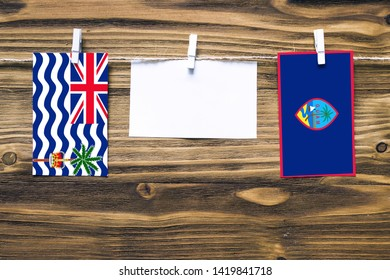 Hanging flags of British Indian Ocean Territory and Guam attached to rope with clothes pins with copy space on white note paper on wooden background.