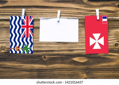 Hanging flags of British Indian Ocean Territory and Wallis And Futuna attached to rope with clothes pins with copy space on white note paper on wooden background.
