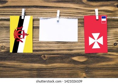 Hanging flags of Brunei and Wallis And Futuna attached to rope with clothes pins with copy space on white note paper on wooden background.Diplomatic relations between countries.