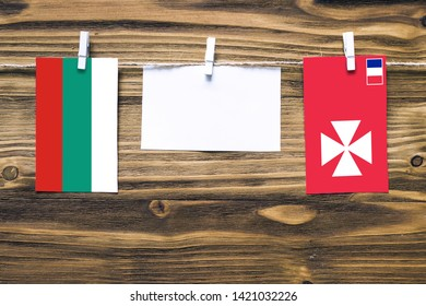 Hanging flags of Bulgaria and Wallis And Futuna attached to rope with clothes pins with copy space on white note paper on wooden background.Diplomatic relations between countries.