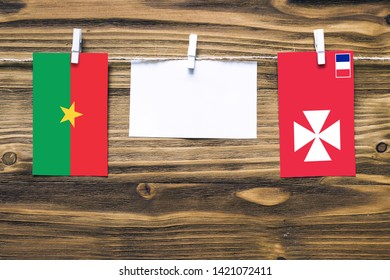 Hanging flags of Burkina Faso and Wallis And Futuna attached to rope with clothes pins with copy space on white note paper on wooden background.Diplomatic relations between countries.