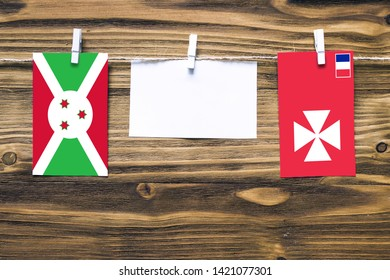 Hanging flags of Burundi and Wallis And Futuna attached to rope with clothes pins with copy space on white note paper on wooden background.Diplomatic relations between countries.