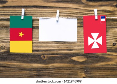 Hanging flags of Cameroon and Wallis And Futuna attached to rope with clothes pins with copy space on white note paper on wooden background.Diplomatic relations between countries.