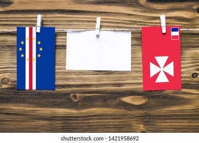 Hanging flags of Cape Verde and Wallis And Futuna attached to rope with clothes pins with copy space on white note paper on wooden background.Diplomatic relations between countries.