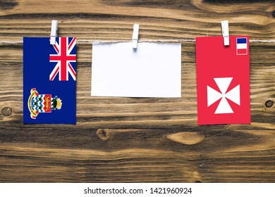 Hanging flags of Cayman Islands and Wallis And Futuna attached to rope with clothes pins with copy space on white note paper on wooden background.Diplomatic relations between countries.
