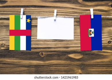 Hanging flags of Central African Republic and Haiti attached to rope with clothes pins with copy space on white note paper on wooden background.Diplomatic relations.