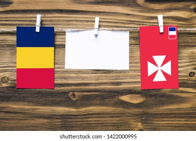 Hanging flags of Chad and Wallis And Futuna attached to rope with clothes pins with copy space on white note paper on wooden background.Diplomatic relations between countries.